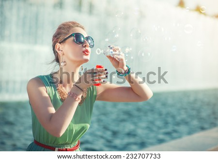 Beautiful girl in vintage clothing blowing bubbles - stock photo