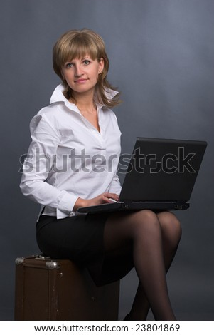 beautiful girl in white blouse and  black skirt sits on suitcase with laptop on her knees on grey background - stock photo