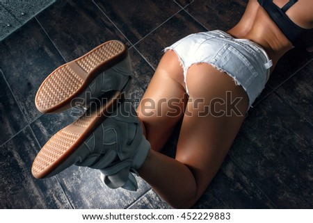 Beautiful girl in white denim shorts and sneakers lying on the floor in the bathroom. She took a provocative pose, showing off sexy ass - stock photo