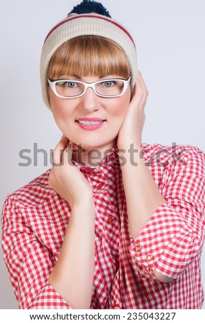 beautiful girl in white galsses and a traditional plaid American shirt, in a cap - stock photo
