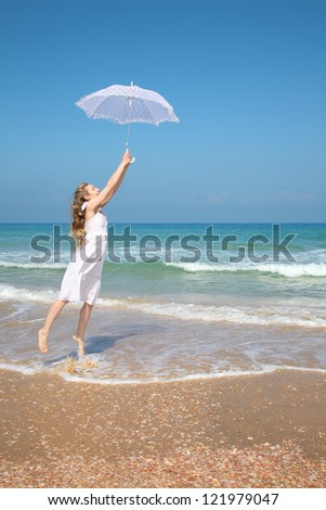 Beautiful girl in white on the beach with umbrella - stock photo