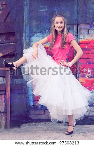 Beautiful girl in white skirt of tulle and a pink shirt, shooting on the street - stock photo