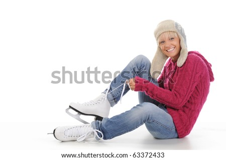 Beautiful girl in winter clothes puts on skates. Isolated on white background - stock photo