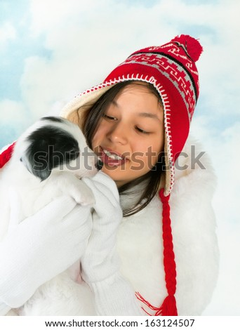 Beautiful girl in winter coat holding a 5 weeks old border collie puppy - stock photo