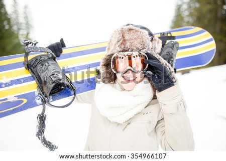 Beautiful girl in winter forest with snowboard and ski mask.Girl snowboarding in the mountains on ski slope.Sport woman in snowy mountains.Young woman holding snowboard.Concept of winter holiday - stock photo