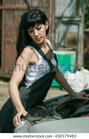 beautiful girl in working overalls mechanic standing near a car with an open hood and thinks in the street - stock photo