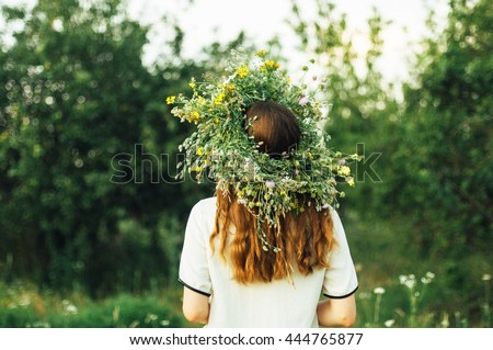 beautiful girl in wreath of flowers  in meadow on sunny day. Portrait of Young beautiful woman wearing a wreath of wild flowers. Young pagan Slavic girl conduct ceremony on Midsummer. Earth Day - stock photo