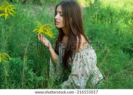 Beautiful girl inhales the aroma of wild flowers - stock photo