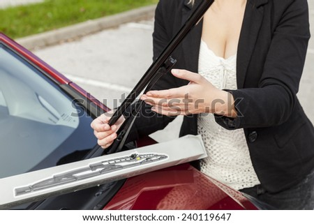 Beautiful girl is changing windscreen wipers on a car - stock photo