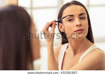 Beautiful girl is doing a makeup, retouching eyebrows while looking at the mirror - stock photo
