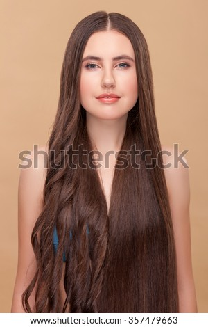 Beautiful girl is experimenting with her long hair. She has curly hair on right side and straight on left one. The lady is standing and smiling. Isolated on brown background - stock photo