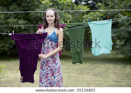 Beautiful girl is hanging laundry on strings. - stock photo