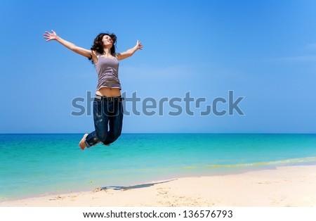 Beautiful girl is having fun on the beautiful tropical beach. Happy jumping woman - stock photo