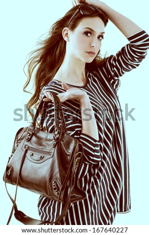 beautiful girl is in fashion style holding bag -light blue background - stock photo