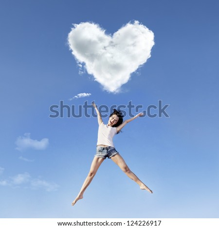 Beautiful girl is jumping under a heart shape cloud - stock photo