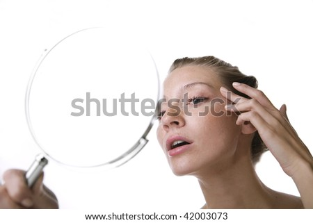 Beautiful girl is looking for first wrinkles. - stock photo