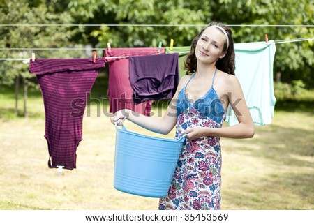 Beautiful girl is making laundry. Focus on face. - stock photo