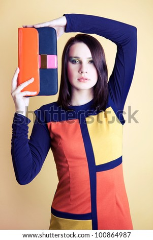 Beautiful girl is posing with colourful bag. Focus on face. - stock photo