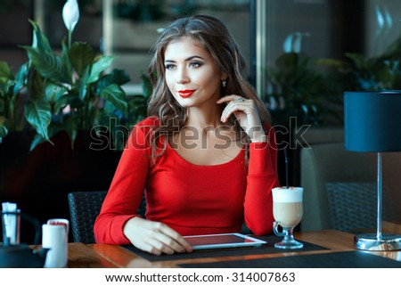 Beautiful girl is sitting in the cafe and thought. On the coffee table, and a tablet. - stock photo