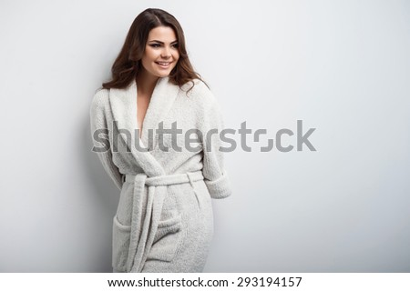 Beautiful girl is smiling and looking aside. She is putting her arms behind her back shyly. Isolated on a grey background and there is copy space in the right side - stock photo