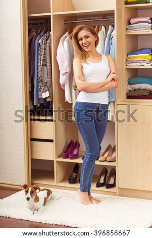 Beautiful girl is smiling and looking at camera, standing with crossed arms in a dressing room. A dog is lying near - stock photo
