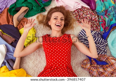Beautiful girl is smiling, lying among high heeled shoes and fashionable clothes on the floor in a dressing room - stock photo