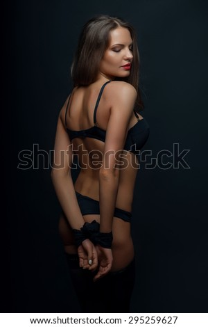 Beautiful girl is standing in attractive underwear. Her arms are tied with rope. She closed her eyes with desire. Isolated on black background - stock photo