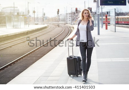 Beautiful girl is walking on the platform an talking on her smart phone - stock photo