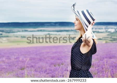 Beautiful girl is wearing stripped hat standing in fairy field of purple lavender. Summer time - stock photo