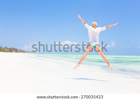 Beautiful Girl Jumping on Beach. Vacation Concept Woman enjoying, relaxing joyfully in summer. Beautiful caucasian model wearing white tunic jumping on picture perfect Paje beach, Zanzibar, Tanzania. - stock photo