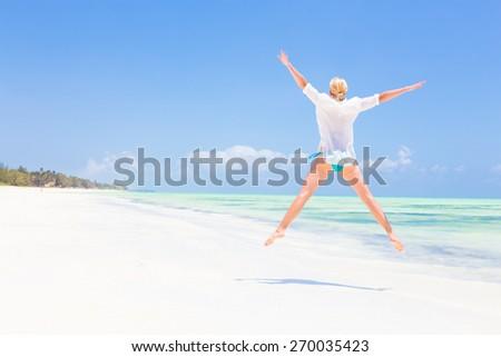 Beautiful Girl Jumping on Beach. Vacation Concept Woman enjoying, relaxing joyfully in summer. Beautiful caucasian model wearing white tunic jumping on picture perfect Paje beach, Zanzibar, Tanzania. - stock photo
