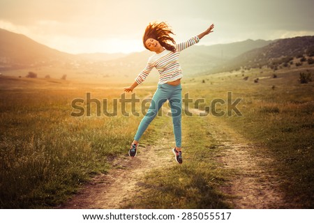Beautiful girl jumping on the rural road. Happiness and freedom concept - stock photo
