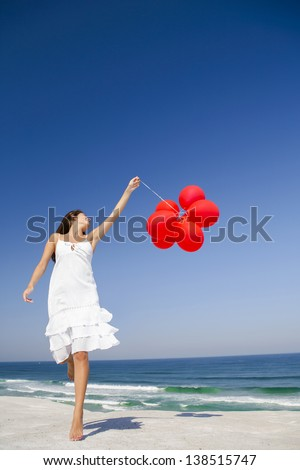 Beautiful girl jumping with red ballons in the beach - stock photo