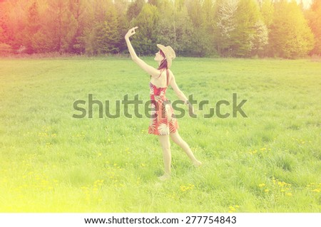 beautiful girl laughs and dances outdoors in a meadow - stock photo