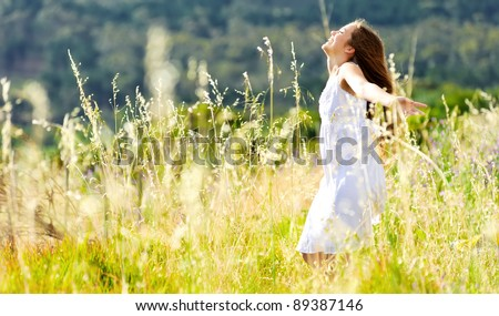 beautiful girl laughs and dances outdoors in a meadow during sunset - stock photo