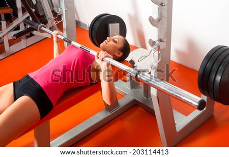 Beautiful girl lifting weights in the gym. - stock photo