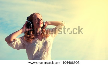 beautiful girl listening to music on headphones in the sky - stock photo