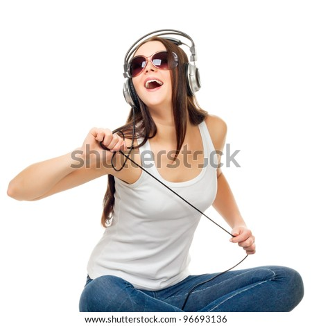 Beautiful girl listens to music through earphones on a white background - stock photo