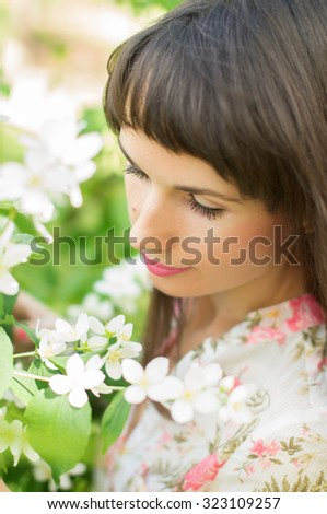 Beautiful girl looking at flowers on nature - stock photo