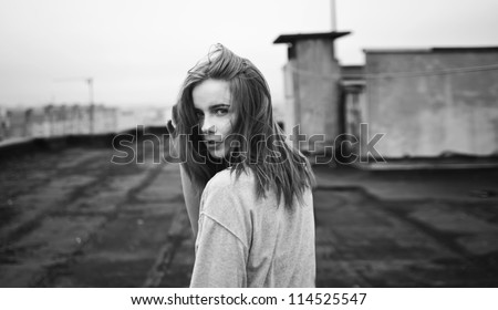 beautiful girl looking back on the roof - stock photo