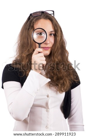 Beautiful girl looking through a magnifying glass - stock photo