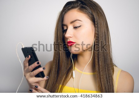 beautiful girl looks at the phone, in a yellow dress, closeup isolated on white background - stock photo