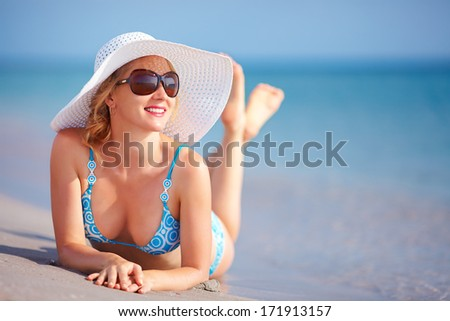 beautiful girl lying in surf on the beach - stock photo