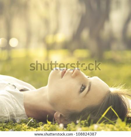 beautiful girl lying on a meadow - stock photo