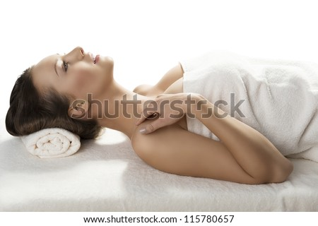 beautiful girl lying on a table with withe towel on her body and under her head, she is in profile, looks in front of her and has the right hand near the right shoulder - stock photo