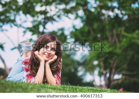 Beautiful Girl lying on green grass. Happy and Smiling. - stock photo