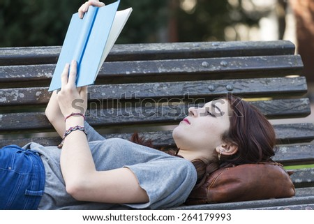 Beautiful girl lying on old wood bench reading blue book in the park, education lifestyle concept. - stock photo