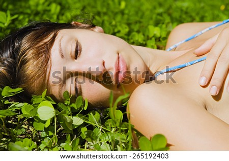 Beautiful Girl lying on the Field.Green Grass - stock photo