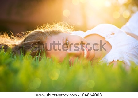 Beautiful Girl lying on the Field.Green Grass. Happy and Smiling - stock photo