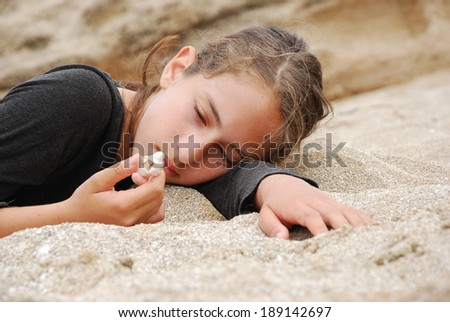Beautiful girl lying on the sand and looking at seashell on her hand - stock photo